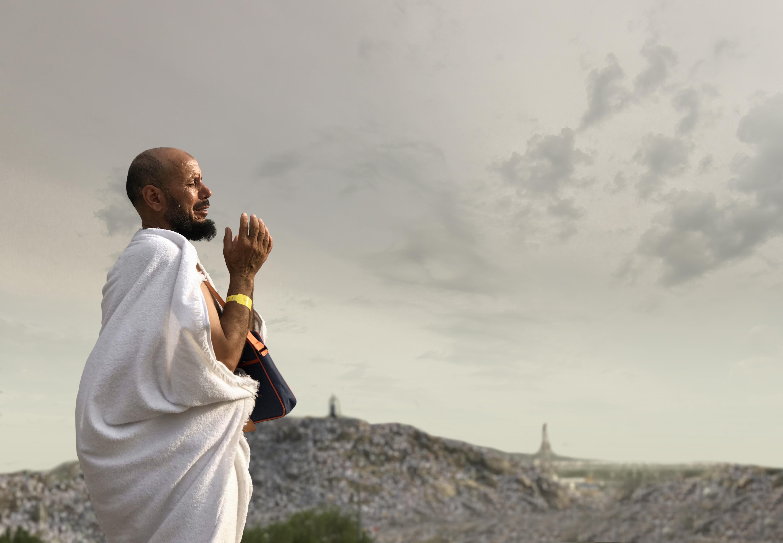 A hajj pilgrim is praying on the mount of Arafat
